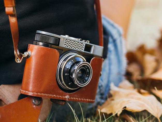 Close-up de uma câmera fotográfica retrô em uma bolsa de couro