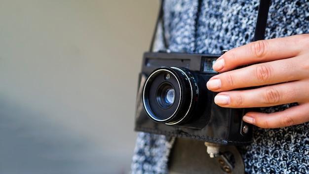 Close-up de uma câmera fotográfica retrô realizada por uma mulher
