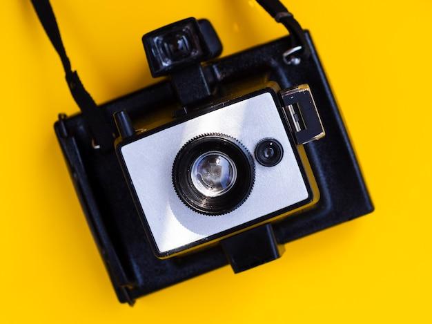 Close-up de uma câmera fotográfica vintage com fundo amarelo