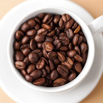 Close-up de uma caneca branca com grãos de café arábica. foto quadrada.