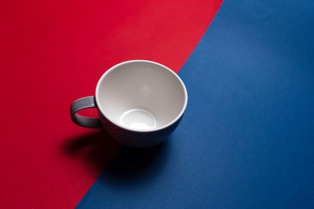 Close-up de uma caneca cinza em duas superfícies de cores vermelhas e azuis