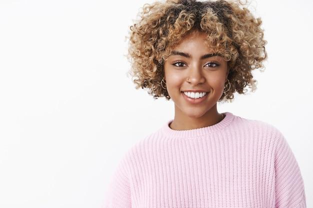Close-up de uma carismática simpática garota feliz de pele escura com piercing no nariz, sorriso perfeito em pé encantado e fofo sobre a parede branca em um suéter desfrutando de um jantar de feriado em família