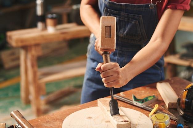 Close-up de uma carpinteira marcando um cinzel com um martelo em uma prancha de madeira para remover pedaços de madeira