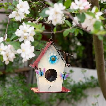 Close-up de uma casa de passarinho colorida em uma parede floral turva