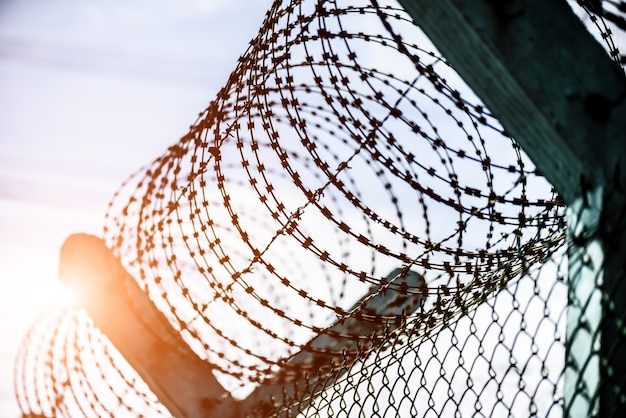 Close up de uma cerca de segurança com arame farpado durante o pôr do sol.