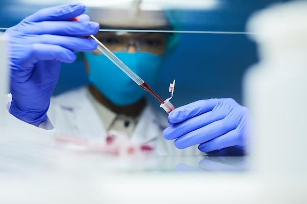 Close-up de uma cientista usando máscara e equipamento de proteção, deixando cair amostras de sangue em tubos de ensaio enquanto trabalhava em pesquisas em laboratório, copie o espaço