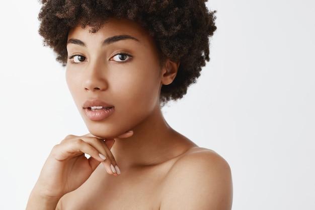 Close-up de uma delicada mulher feminina de pele escura com cabelo encaracolado, tocando o queixo suavemente com os dedos, abrindo a boca sensualmente e olhando nua
