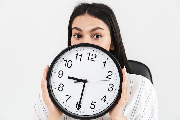 Close-up de uma empresária animada mostrando um despertador isolado sobre uma parede branca