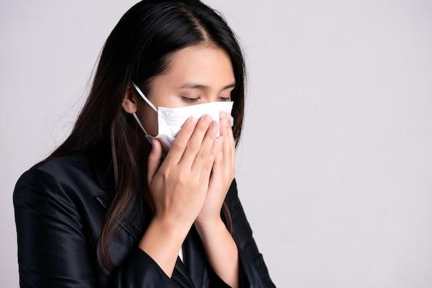 Close-up de uma empresária em um terno usando máscara protetora e tosse