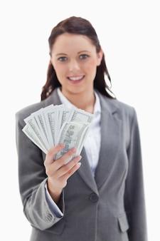 Close-up de uma empresária sorrindo e segurando muitos dólares em notas de banco