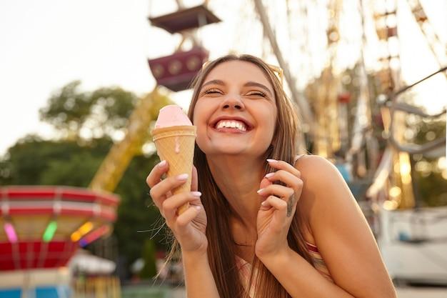 Close-up de uma encantadora jovem morena alegre com óculos de sol na cabeça, mostrando os dentes e sorrindo alegremente enquanto come uma casquinha de sorvete rosa sobre um parque de diversões