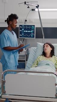 Close-up de uma enfermeira afro-americana monitorando uma mulher doente enquanto descansava na cama na enfermaria do hospital