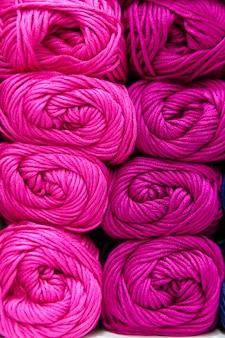 Close-up de uma escala de fios de lã rosa organizados por cor e armazenamento em uma prateleira