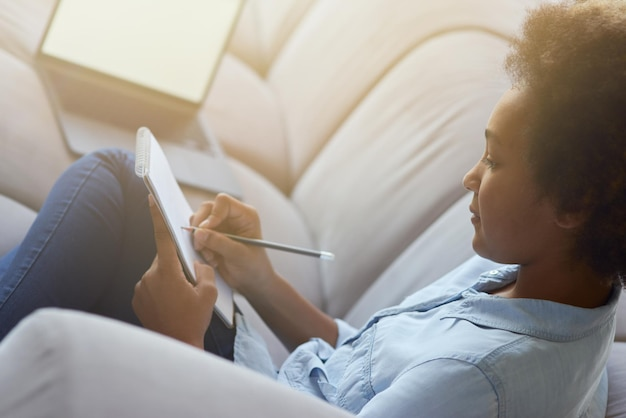 Close-up de uma estudante adolescente de raça mista usando lápis para fazer anotações enquanto faz o dever de casa