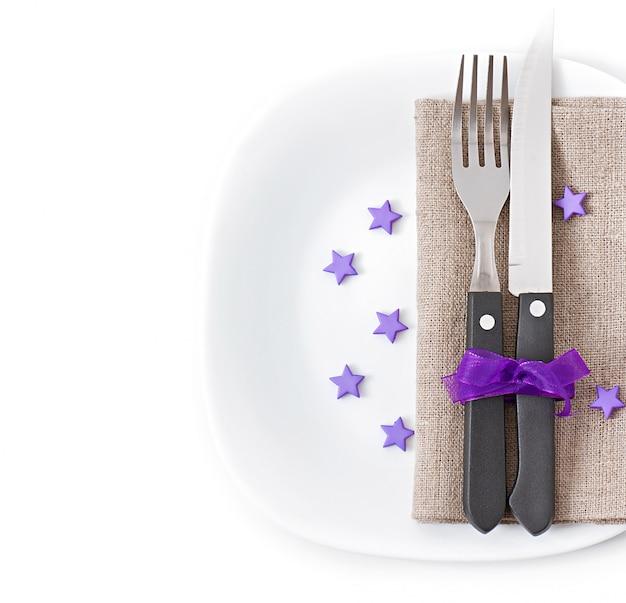 Close-up de uma faca e um garfo em um prato branco com guardanapo