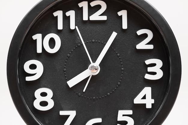 Close-up de uma face do relógio de parede preta sobre fundo branco