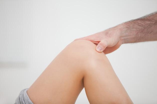 Close up de uma fisioterapeuta tocando um joelho