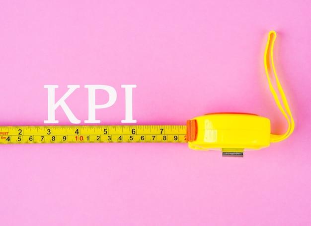 Close up de uma fita de medição com palavra do indicador de desempenho chave.