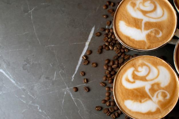 Close-up de uma flor de desenho no café, latte art em um fundo de grãos de café em uma mesa