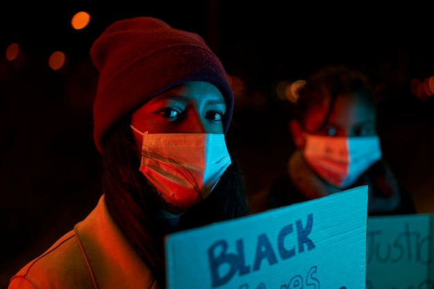 Close-up de uma garota afro-americana segurando uma bandeira em pé no meio de uma multidão de manifestantes.