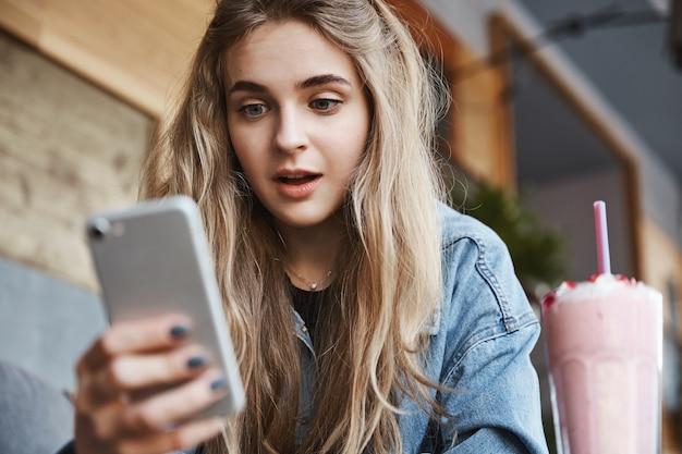 Close-up de uma garota animada olhando para a tela do smartphone ao ar livre