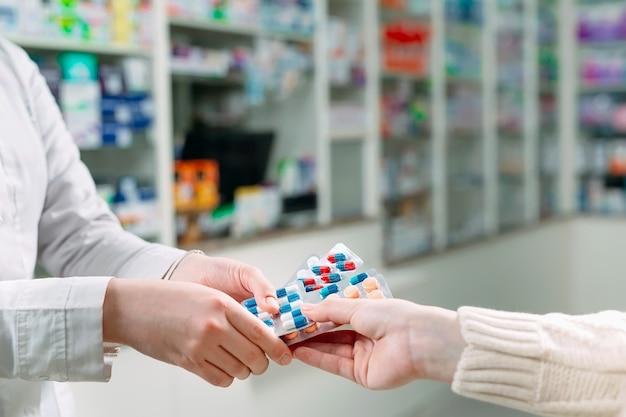 Close-up de uma garota com as mãos comprando comprimidos em uma farmácia