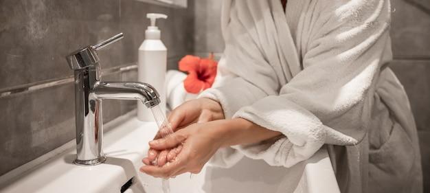 Close up de uma garota em um roupão de banho lava as mãos no banheiro.