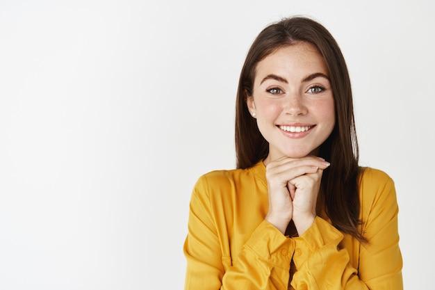 Close-up de uma garota feliz e sonhadora, olhando para a câmera com admiração, apoiando-se nas mãos e ouvindo com interesse, em pé sobre uma parede branca