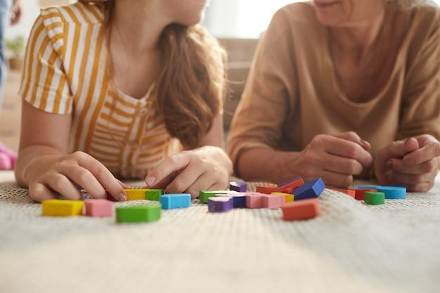 Close-up de uma garota irreconhecível brincando com blocos coloridos enquanto estava deitada no chão com a vovó no interior de uma casa aconchegante