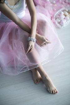 Close-up de uma garota pulsos nus e pernas em um vestido longo sem rosto