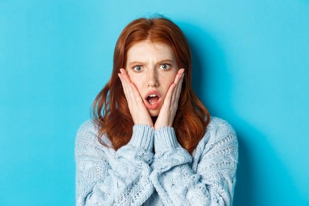 Close-up de uma garota ruiva chocada, olhando para algo desagradável, segurando as mãos no rosto e ofegando, em pé sobre um fundo azul.