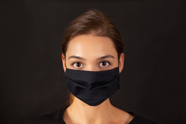 Close-up de uma garota usando uma máscara facial de pano preto durante uma pandemia de covid-19.