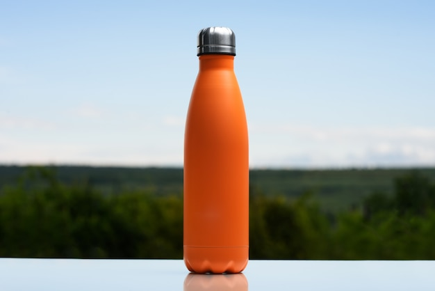 Close-up de uma garrafa de água térmica ecológica reutilizável com tampa prateada, cor lava exuberante