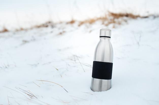 Close-up de uma garrafa de água térmica reutilizável de aço na neve.