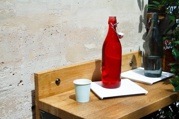 Close-up de uma garrafa de água vermelha e vidro em uma mesa de restaurante contra uma parede de pedra clara