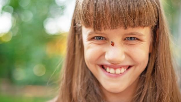 Close-up de uma joaninha no rosto de uma pequena menina sorridente.