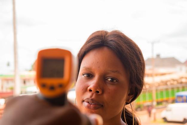 Close-up de uma jovem africana usando o termômetro infravermelho para a testa (pistola de termômetro) para verificar se há sintomas de vírus em sua temperatura corporal - conceito de surto de vírus epidêmico