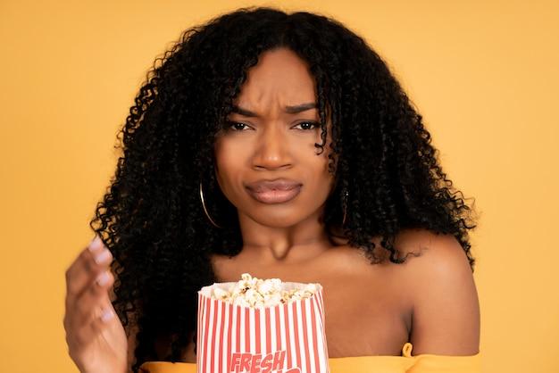 Close-up de uma jovem afro, assistindo filmes enquanto come pipoca, contra um fundo isolado.