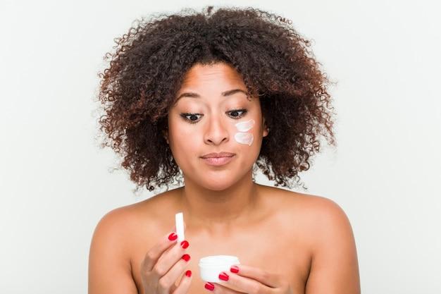 Close-up de uma jovem americana africano, aplicar um creme hidratante