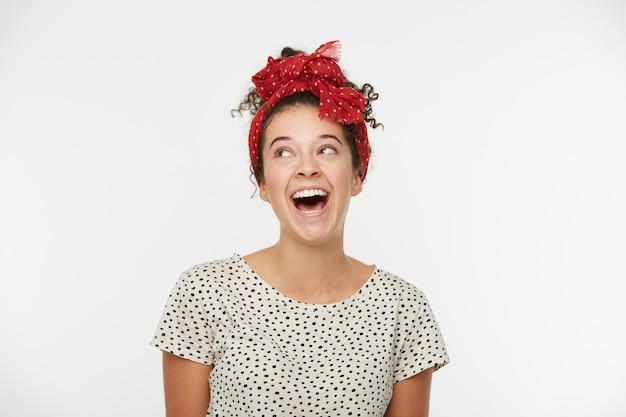 Close up de uma jovem atraente e fofa desvia o olhar rindo, sorrindo, parece boneca, flerta, usa camiseta e lenço vermelho com bolinhas