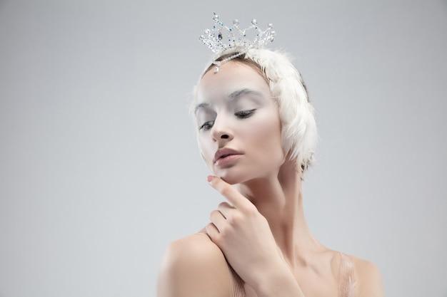 Close-up de uma jovem bailarina graciosa no fundo branco do estúdio