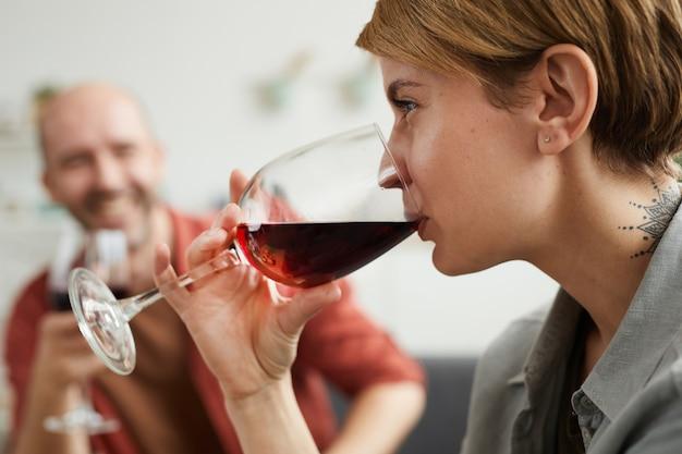 Close-up de uma jovem bebendo vinho tinto em uma taça de vinho com o homem sentado