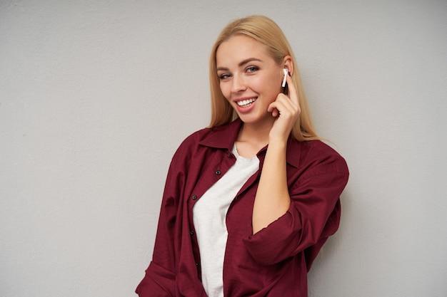 Close-up de uma jovem bonita de olhos azuis e cabelos loiros compridos, usando fones de ouvido e mantendo o dedo indicador no fone de ouvido, sorrindo amplamente enquanto posava sobre um fundo cinza claro