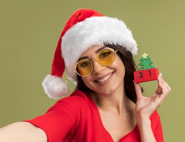 Close-up de uma jovem bonita sorridente com chapéu de papai noel e óculos segurando um brinquedo da árvore de natal com uma data esticando a mão isolada na parede verde oliva