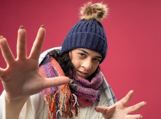 Close-up de uma jovem caucasiana doente e confiante usando um manto, chapéu de inverno e lenço embrulhado em manta, esticando as mãos com gesso no nariz, isolado na parede vermelha