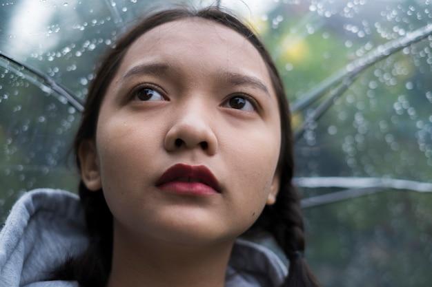 Close-up de uma jovem com um guarda-chuva sob a chuva em um parque