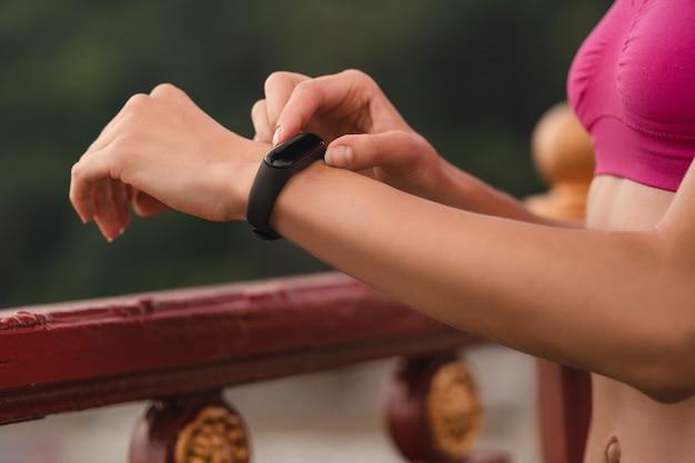 Close-up de uma jovem com um monitor de fitness medindo a frequência cardíaca após um treino intenso ao ar livre