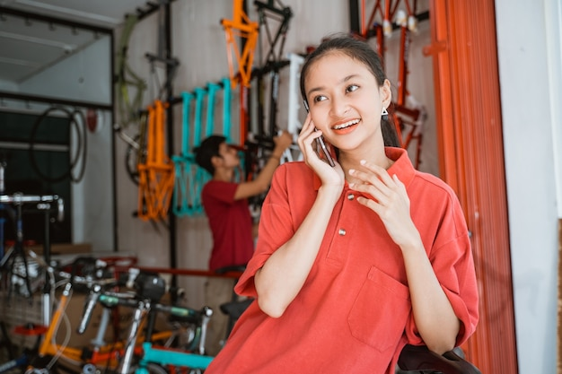 Close-up de uma jovem conversando usando um telefone celular em pé