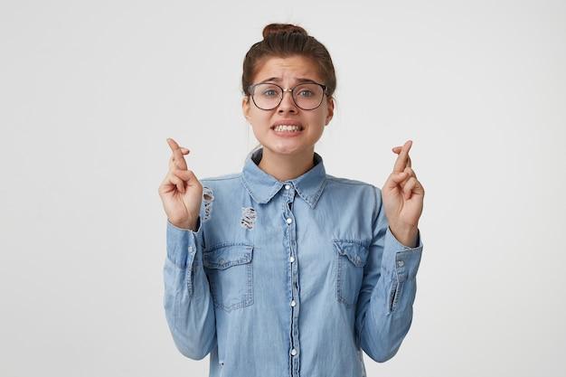 Close-up de uma jovem de óculos fica com os olhos fechados, mãos para cima e dedos cruzados