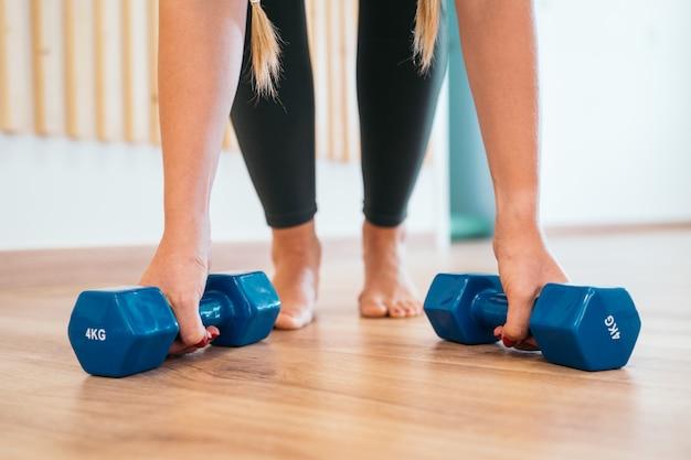 Close-up de uma jovem desportiva fazendo exercícios de flexões com halteres no chão de madeira